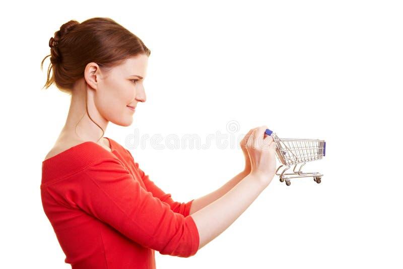 Donna che tiene un piccolo carrello di acquisto fotografia stock