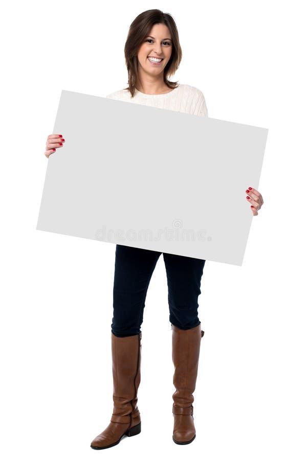 Donna che tiene un segno bianco in bianco immagini stock