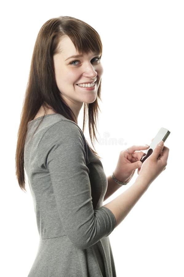 Donna che tiene un telefono delle cellule su priorità bassa bianca fotografia stock libera da diritti