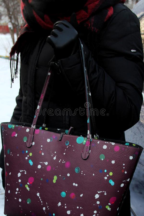 Donna che tiene una borsa porpora con i punti colorati sulla sua mano borsa porpora con le macchiette che appendono sulla mano di immagine stock