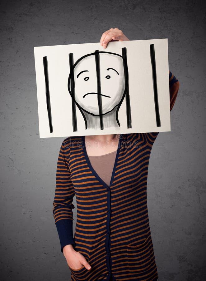 Donna che tiene una carta con un prigioniero dietro le barre su nella f immagine stock libera da diritti