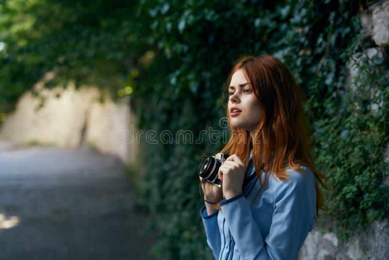 Donna che tiene una macchina fotografica sulla via immagine stock