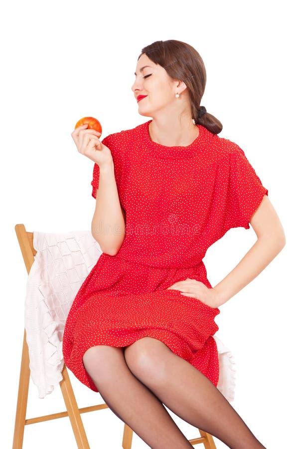 Donna che tiene una mela che si siede su una sedia fotografie stock libere da diritti