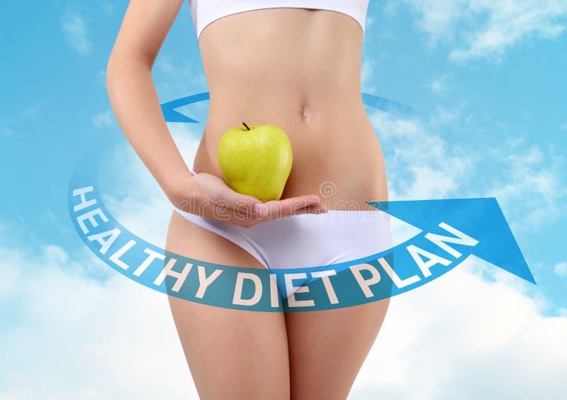 Donna che tiene una mela con le mani vicino alla pancia, concetto di dieta immagini stock