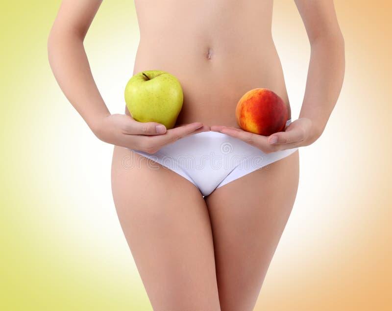 Donna che tiene una mela e una pesca con le sue mani vicino alla pancia immagini stock libere da diritti
