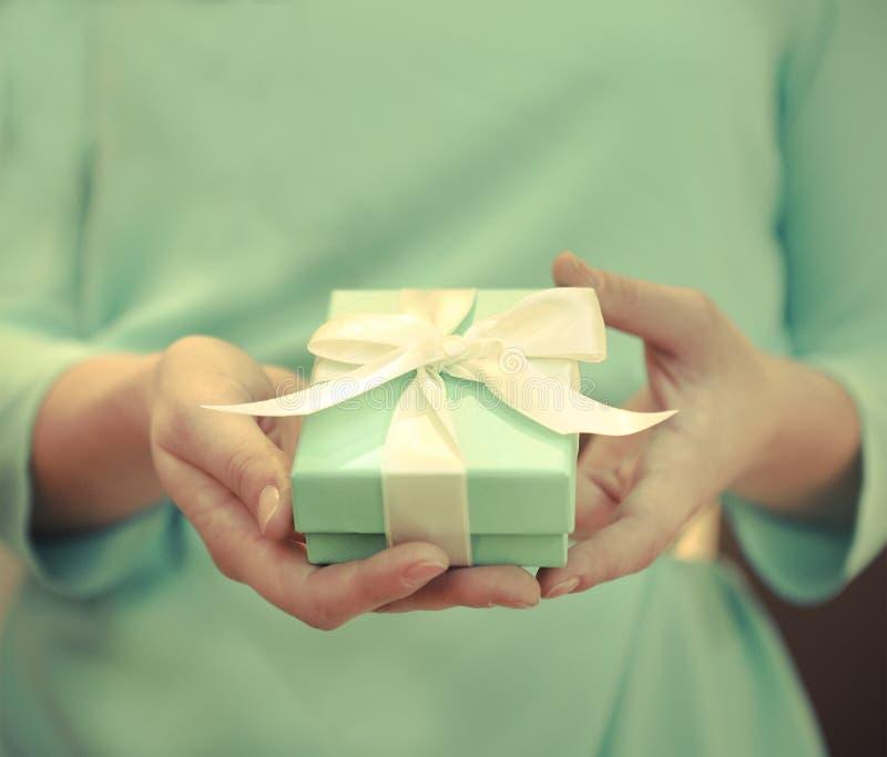 Donna che tiene una piccola scatola blu con un nastro bianco fotografia stock