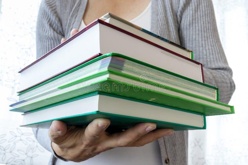 Donna che tiene una pila di libri in alto vicino delle mani, nell'istruzione e nel concetto della scuola fotografia stock
