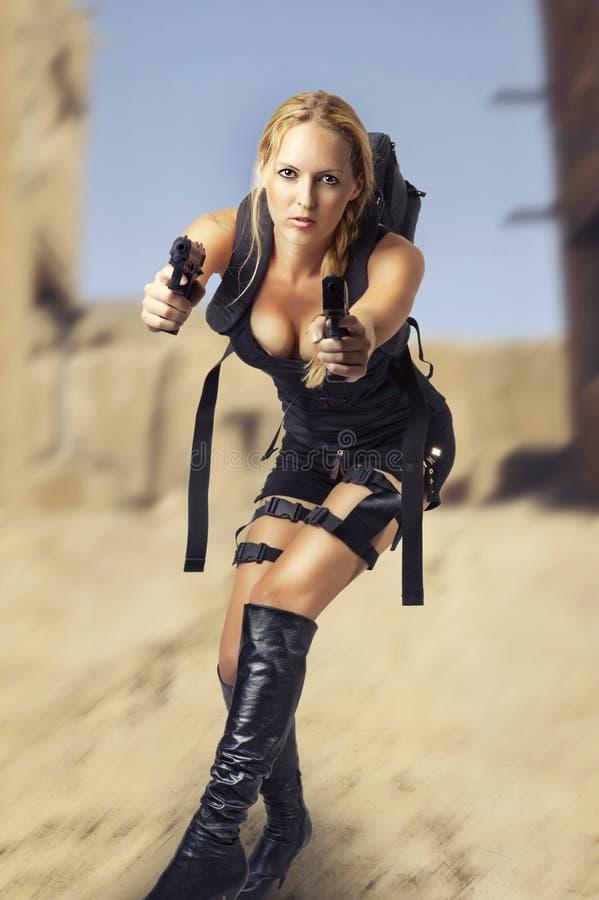 Donna che tiene una pistola delle due mani immagine stock libera da diritti