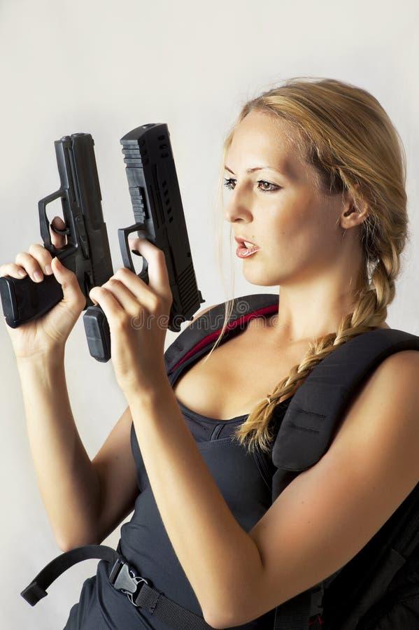 Donna che tiene una pistola delle due mani fotografia stock
