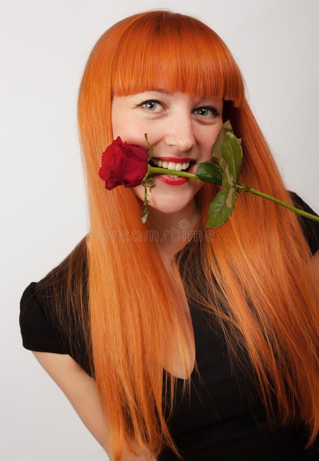 Donna che tiene una rosa nella sua bocca fotografia stock libera da diritti
