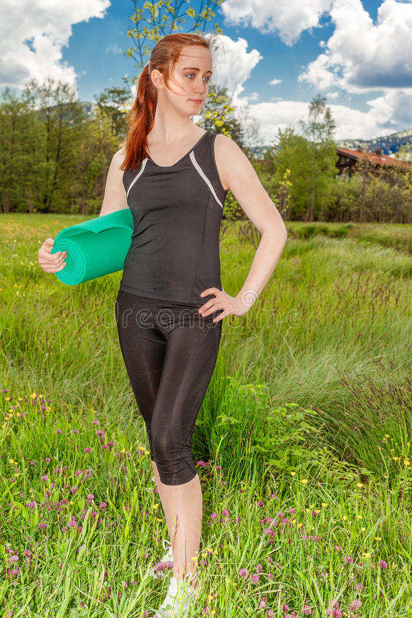 Donna che tiene una stuoia acciambellata di esercizio fotografia stock libera da diritti
