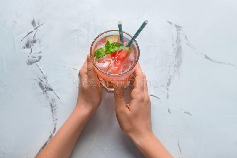 Donna che tiene vetro della limonata fredda saporita dell'anguria sulla tavola leggera immagini stock libere da diritti