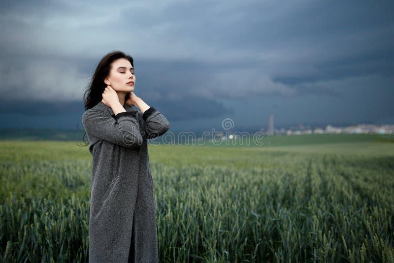 Donna che tocca collo con gli occhi chiusi sotto il cielo nuvoloso nel campo Vista orizzontale immagini stock libere da diritti