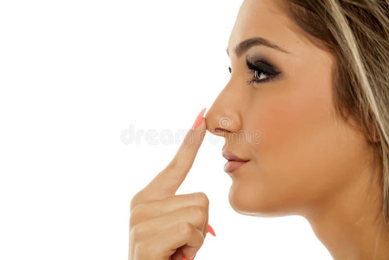 Donna che tocca il suo naso fotografie stock