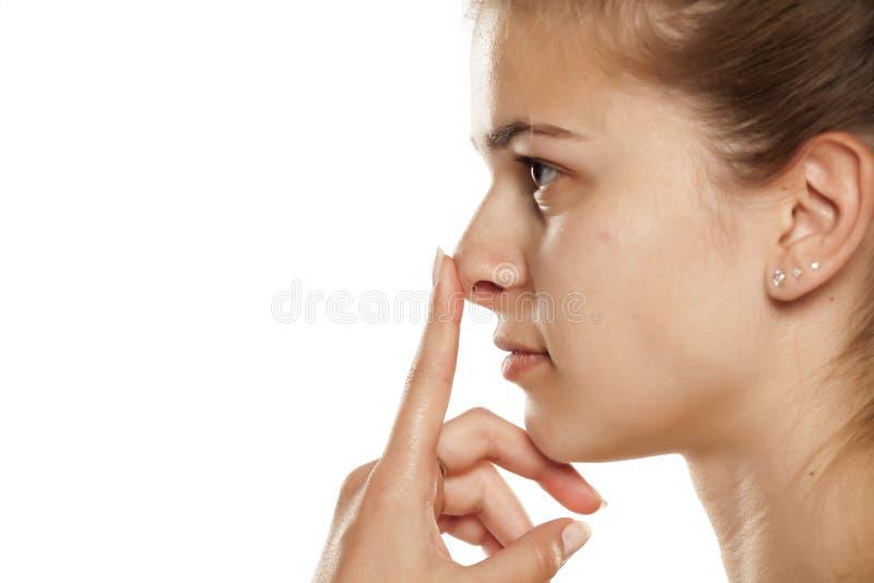 Donna che tocca il suo naso immagine stock