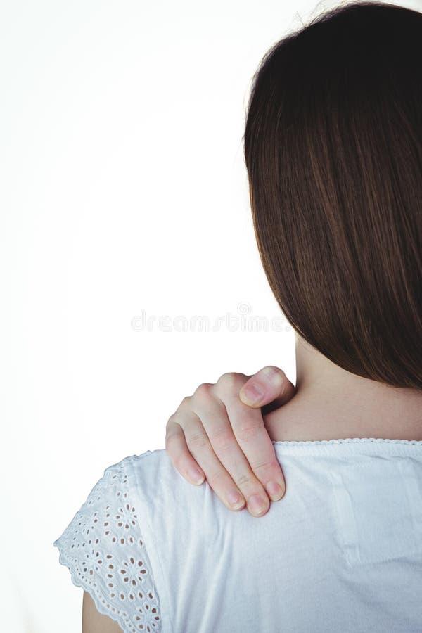 Donna che tocca la sua spalla irritata immagini stock