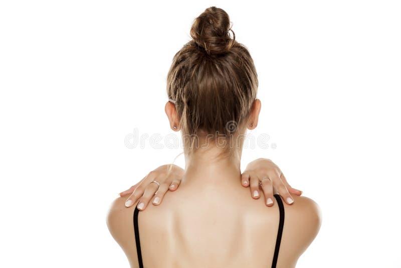 Donna che tocca le sue spalle fotografia stock