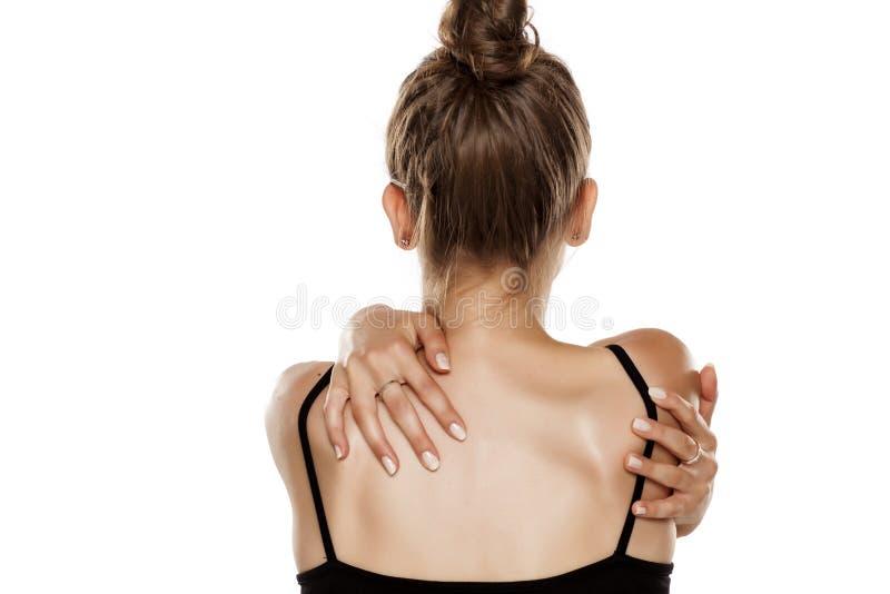 Donna che tocca le sue spalle fotografia stock libera da diritti