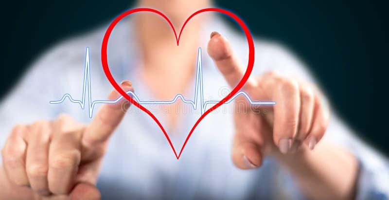 Donna che tocca un grafico dei battiti cardiaci fotografia stock