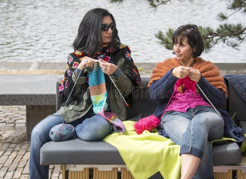 Donna che tricotta un giorno di multiculture del outsideon del sofà in Olanda fotografia stock libera da diritti
