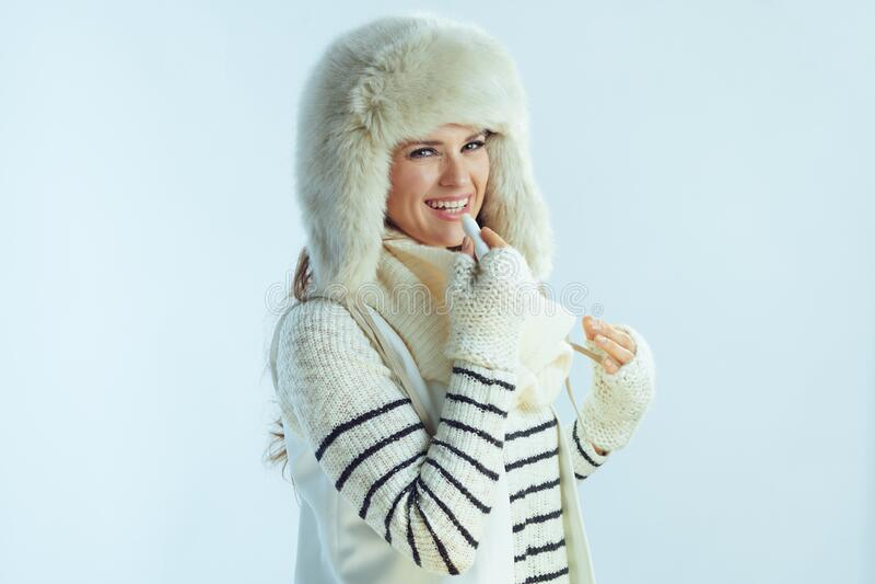 Donna che usa rossetto igienico su fondo blu chiaro invernale fotografia stock libera da diritti