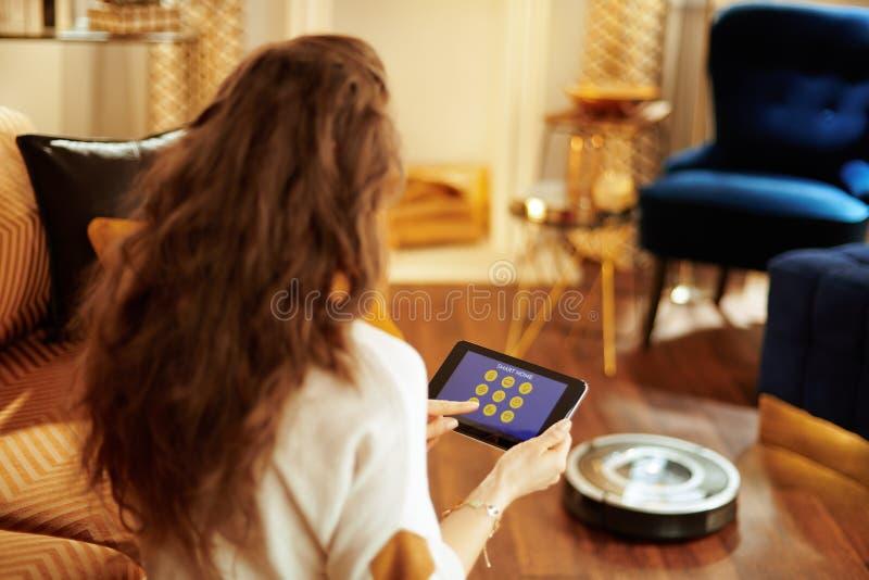 Donna che usando applicazione domestica astuta sul vuoto del PC e del robot della compressa immagini stock