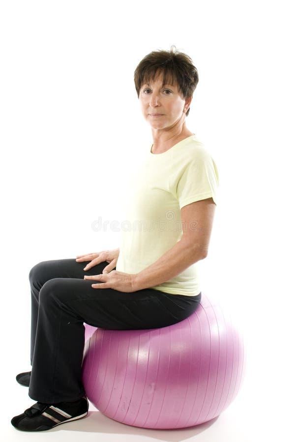 Donna che usando esercitazione della sfera di forma fisica di addestramento di memoria immagini stock