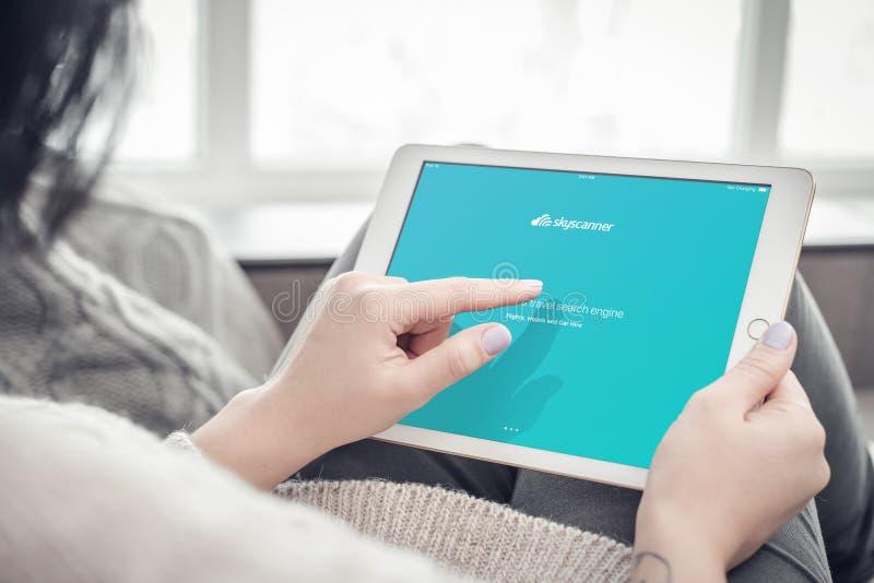 Donna che usando i apps di Skyscanner su un iPad nuovissimo di Apple pro fotografie stock
