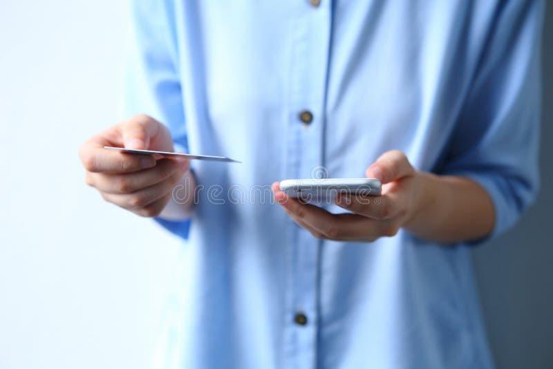 Donna che usando la carta di credito che paga soldi via lo shopp online dello smartphone fotografie stock libere da diritti