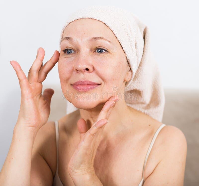 Donna che usando la crema di fronte immagine stock libera da diritti