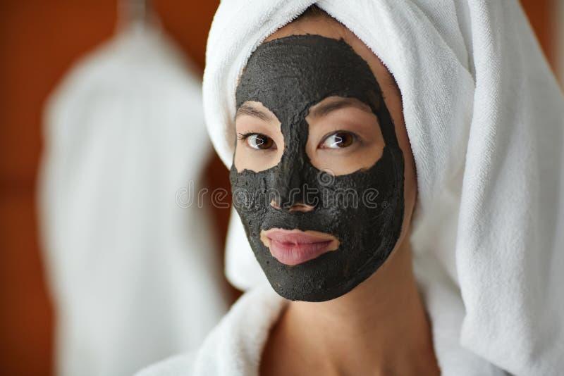 Donna che usando la maschera di protezione di pulizia della pelle fotografie stock