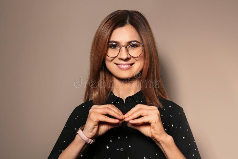 Donna che usando linguaggio dei segni su fondo fotografia stock libera da diritti