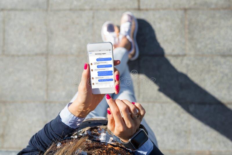 Donna che usando messaggistica immediata app sul telefono cellulare immagine stock