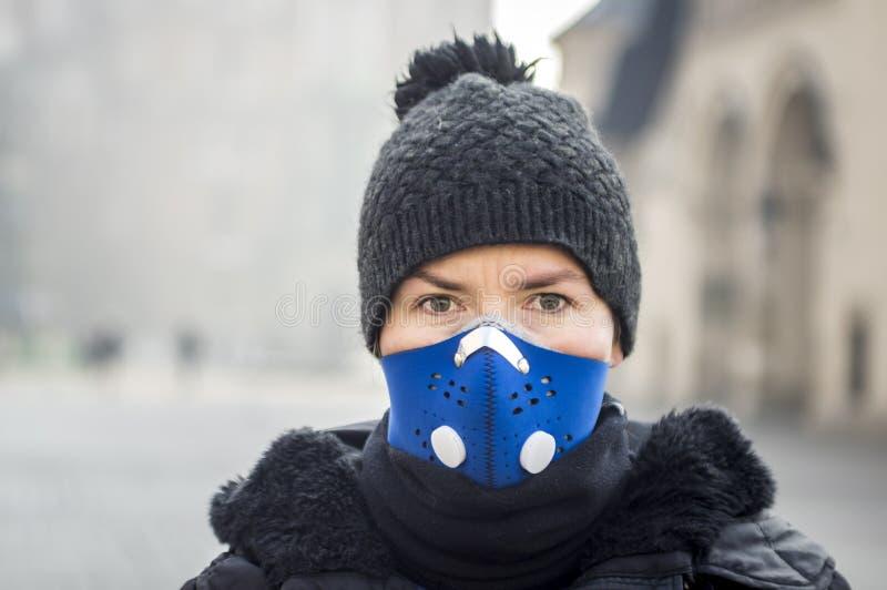 Donna che usando una maschera, proteggentesi dallo smog fotografie stock