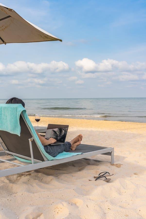 Donna che utilizza computer portatile mentre rilassandosi sulla spiaggia nell'estate fotografie stock