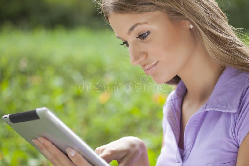 Donna che utilizza il calcolatore del ridurre in pani nella sosta immagini stock libere da diritti