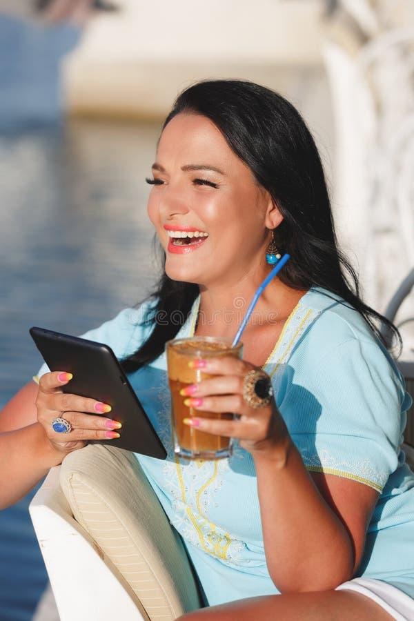 Donna che utilizza il computer della compressa nella caffetteria fotografia stock