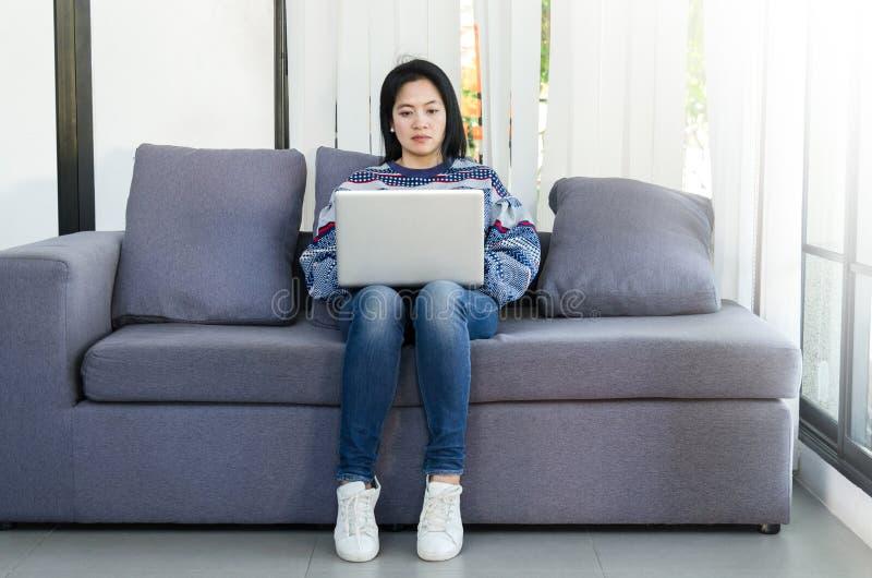 Donna che utilizza il computer portatile del computer sul sofà nella sua casa immagine stock