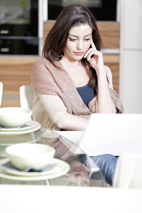 Donna che utilizza il suo computer portatile nella cucina fotografia stock libera da diritti