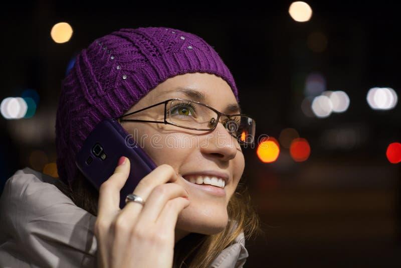 Donna che utilizza smartphone nella città di notte fotografia stock libera da diritti