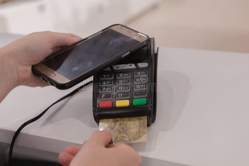 Donna che utilizza tecnologia di NFC per il pagamento nel negozio immagini stock