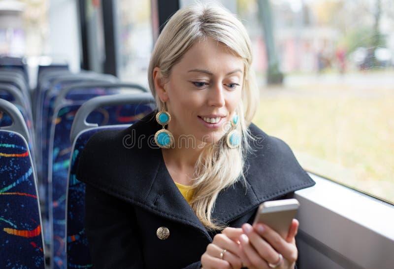 Donna che utilizza telefono cellulare mentre guidando nel trasporto pubblico fotografia stock