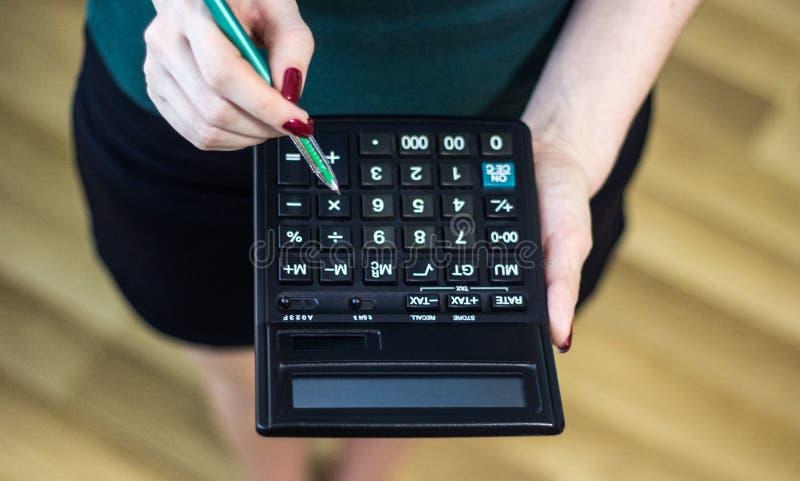 Donna che utilizza un calcolatore con una penna nella sua mano, ufficio calcolatore di spesa finanziaria a casa immagini stock