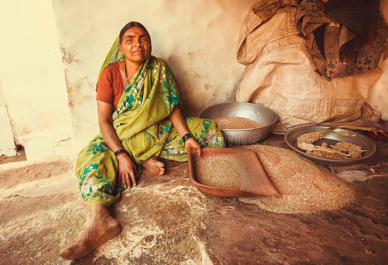 Donna che vaglia grano alla sua casa rurale in villaggio indiano fotografia stock