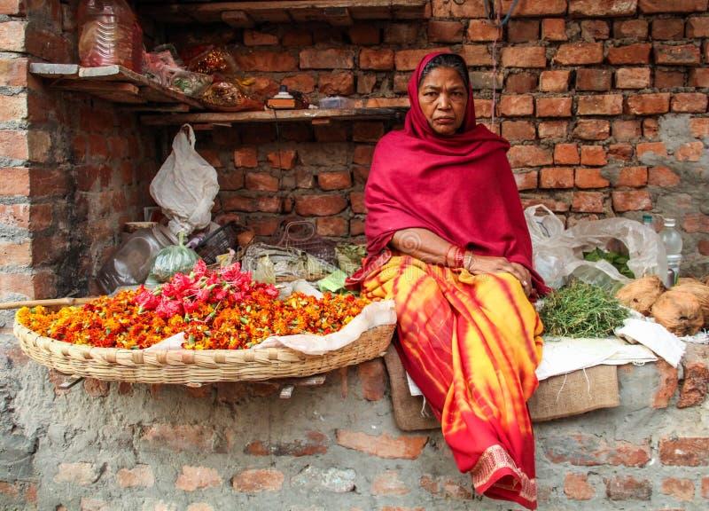 Donna che vende i fiori e le erbe nel primo mattino, a Varanasi Benares, Uttar Pradesh, India immagini stock
