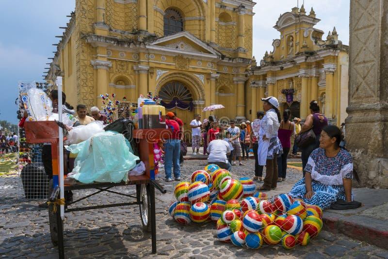 Donna che vende vendendo le palle di gomma variopinte in una via di vecchia città dell'Antigua con il San Pedro Hospital sui prec fotografie stock