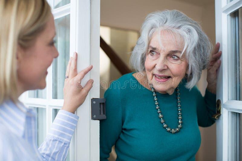 Donna che verifica il vicino femminile anziano fotografia stock libera da diritti