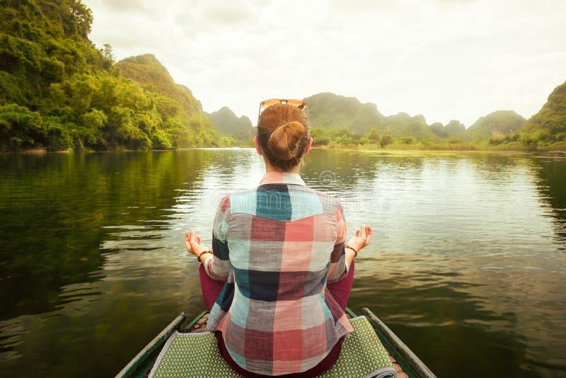 Donna che viaggia in barca sul fiume in mezzo del mountai scenico di morfologia carsica fotografia stock libera da diritti