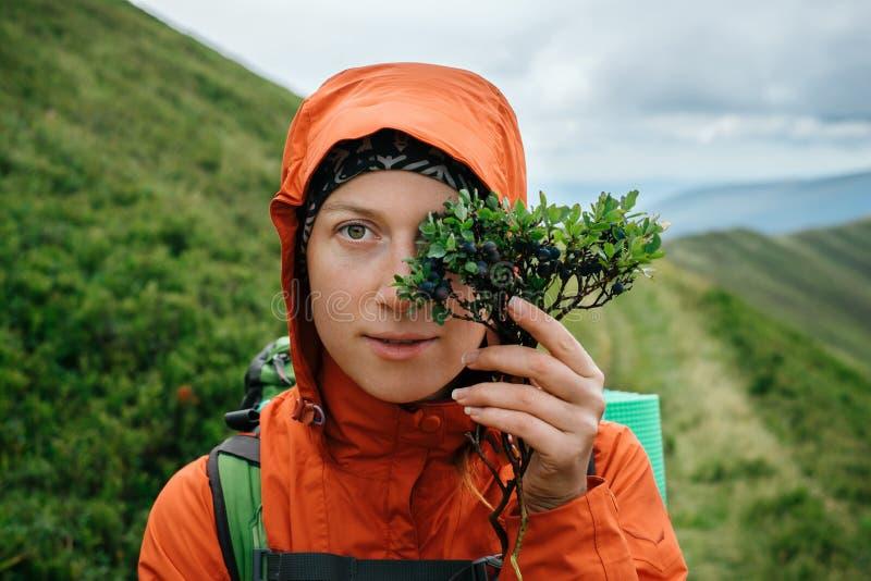 Donna che viaggia in montagna e che gode dei mirtilli del locale di gusto fotografia stock libera da diritti