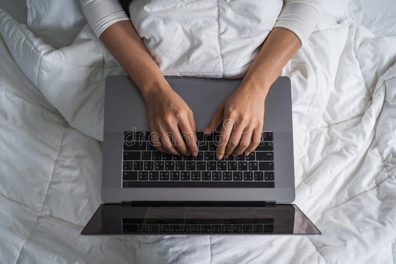 Donna chiusa-su che per mezzo del computer portatile sul letto immagini stock